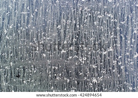 A glass covered with ice crystals in rows as a background texture