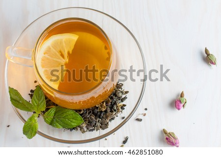 A glass cup of green natural tea with ginger, lemon, mint and honey on wooden rustic background. Healthy drink.