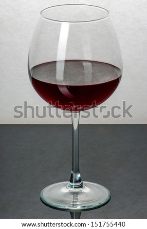 A glass filled with wine on a black reflective surface