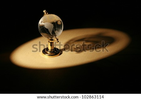 a glass globe in dramatic lighting............ - stock photo