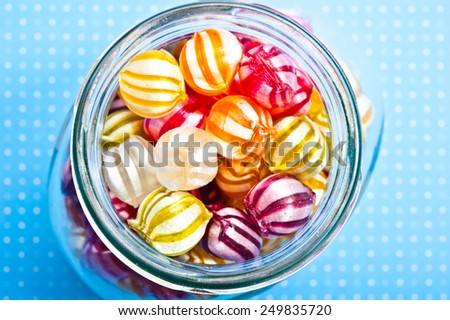 a glass jar filled with colorful candies - stock photo