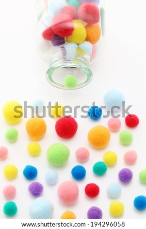 A glass jar filled with felt balls and some that spilled out. - stock photo