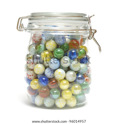 A glass jar is full of various marbles.