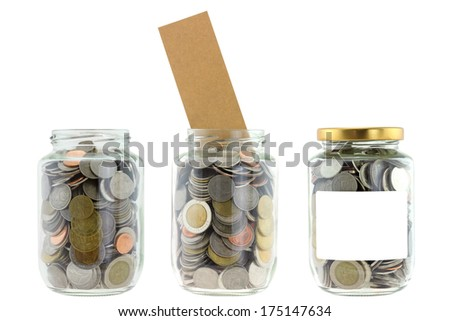 A glass jar with blank label full of many coins, saving money isolated on white background - stock photo