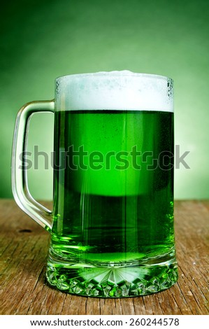 a glass mug with dyed green beer on a rustic wooden surface - stock photo