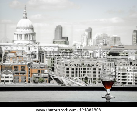 A glass of beer and a view from Tate Modern gallery's cafe on St Paul Cathedral with Millennium Bridge over Thames river. London, England. Reflections. Aged photo. - stock photo