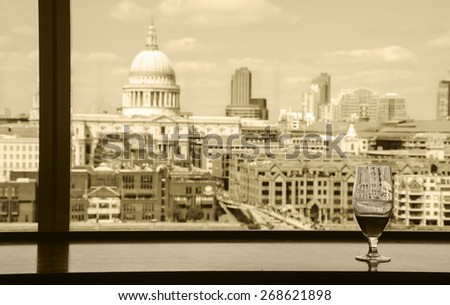 A glass of beer and a view from Tate Modern gallery's cafe on St Paul Cathedral with Millennium Bridge over Thames river. London, England. Reflections. Aged photo. Sepia. - stock photo