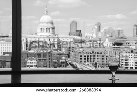 A glass of beer and a view from Tate Modern gallery's cafe on St Paul Cathedral with Millennium Bridge over Thames river. London, England. Reflections. Aged photo. Black and white. - stock photo
