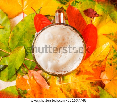 A glass of beer on a background autumn leaves - stock photo