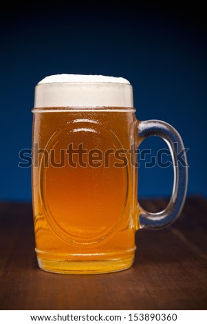 A glass of beer on a wooden table. - stock photo
