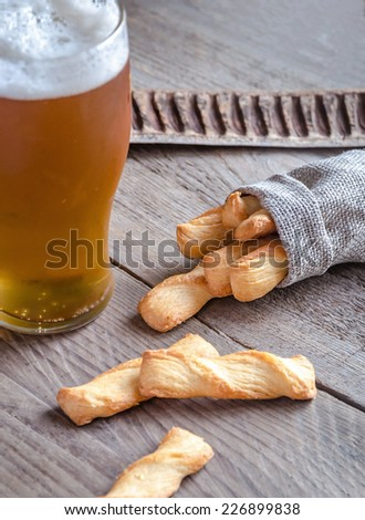 A glass of beer with breadsticks - stock photo