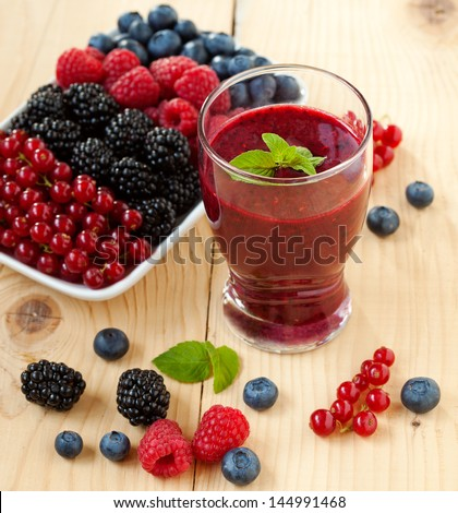 A glass of berry smoothie with fresh fruits, shallow depth of field - stock photo