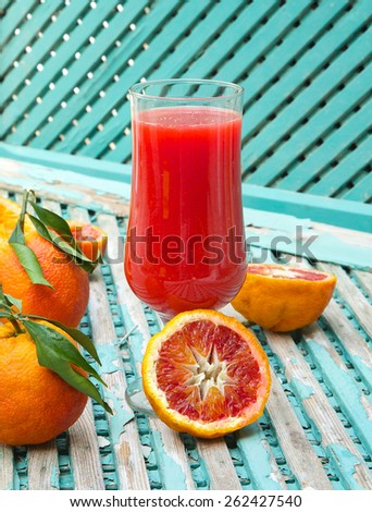 A glass of blood oranges fresh juice on a old green surface. Oranges in the background