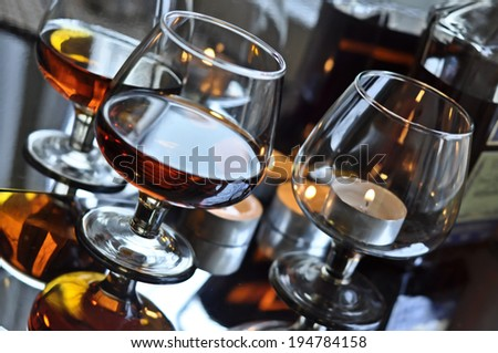 a glass of brandy and a candle, reflection - stock photo