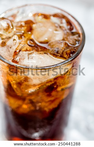 a glass of brown soda with ice cubes - stock photo