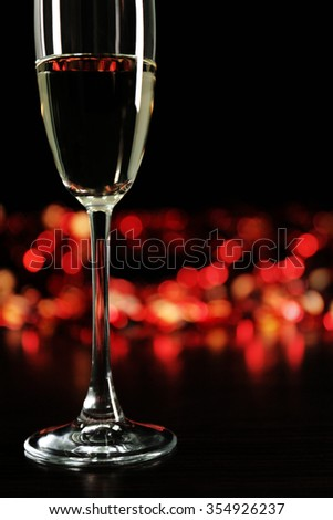 A glass of champagne with bokeh on dark background