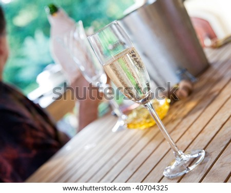 a glass of champagne with countryside background