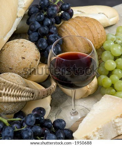 A glass of Chianti wine with assorted breads, cheese and grapes - stock photo