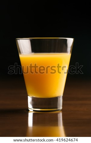 A glass of chilled orange juice on a black background