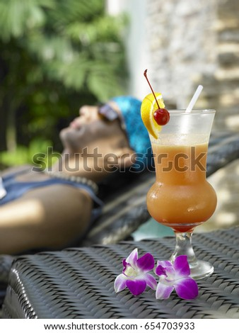 A glass of cocktail with man relaxing in the background