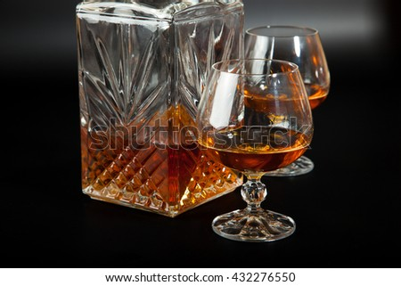A glass of cognac on black background
