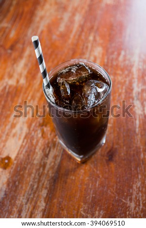 A glass of cola with ice on old wood textured.