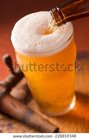A glass of cold beer being poured on top of a rustic keg with antique spigot. - stock photo