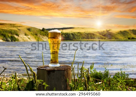 a glass of cold beer on the beach at sunset - stock photo