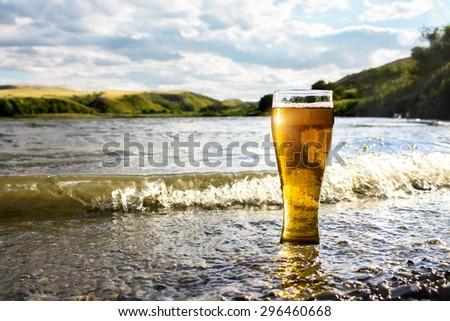 a glass of cold beer on the sea shore - stock photo