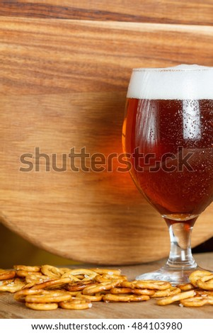 A glass of cold foamy beer with pretzels. Traditional german Oktoberfest food and drink on wooden background