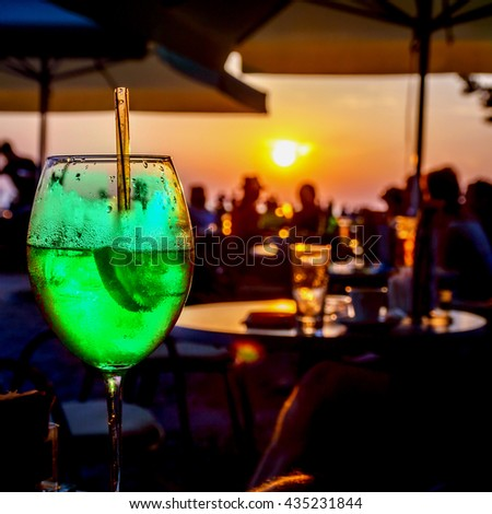 A glass of cold neon green cocktail at the sunset on the table of a beach bar at the sunset, with blurry people around having refreshments or partying on a summer evening, with copy space for text - stock photo