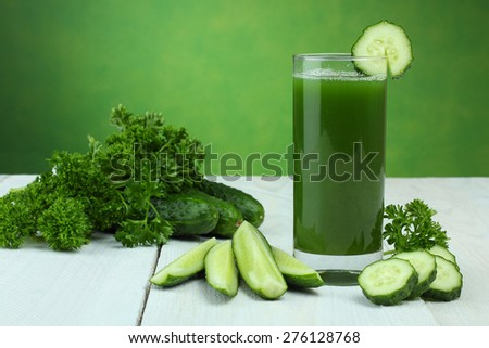A glass of cucumber juice and fresh cucumber on a wooden table - stock photo