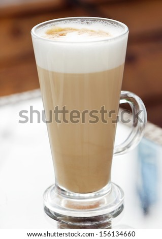 A glass of delicious cold coffee with foam and cinnamon on a table - stock photo