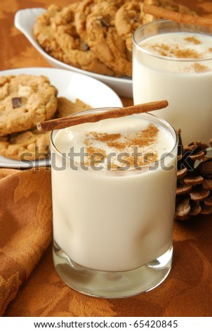 A glass of eggnog with cinnamon and peanut butter cookies - stock photo