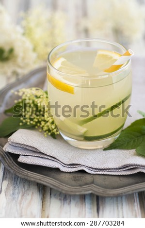 A glass of elderflower cordial with lime and lemon