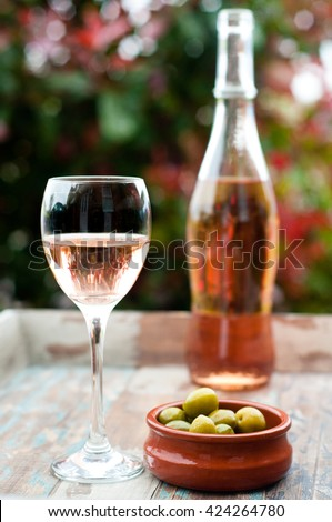 A glass of French rose wine with some fresh green olives served on a rustic wooden table in the garden.