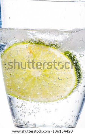 a glass of fresh drinking water and a lime. mineral water as a thirst quencher. - stock photo