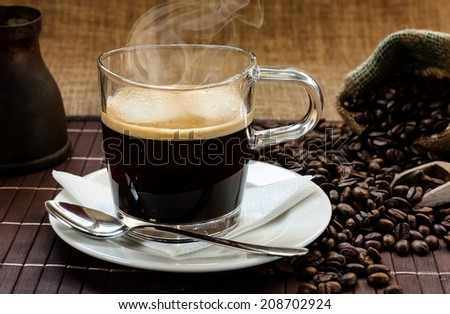 A glass of fresh, hot and steamy espresso coffee on a white plate with a napkin and a spoon, with a sack of coffee beans in the background - stock photo