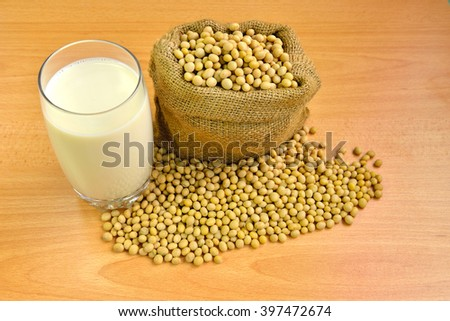 A glass of fresh soy milk and soy beans isolated on wooden texture background, selective focus.  - stock photo