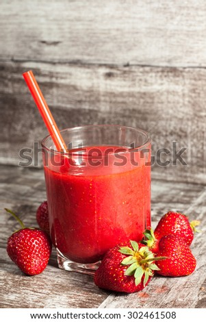 A glass of fresh strawberry smoothie on a wooden background. Summer drink and refreshment organic concept.