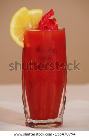 A glass of fresh tomato juice with lemon wedges - stock photo