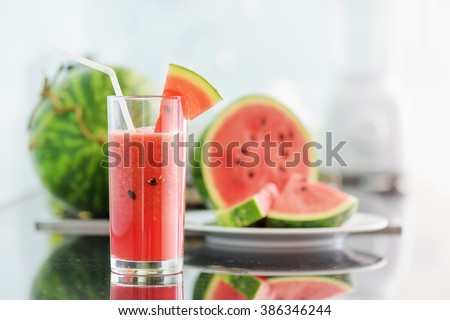 A glass of fresh watermelon juice on table in kitchen. Ripe watermelons and slices in background. A healthy eco food rich in vitamins. A popular product of organic farming. - stock photo