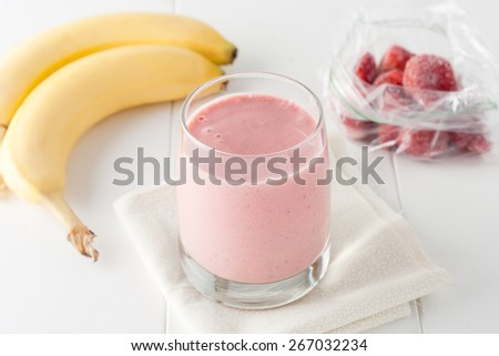 a glass of homemade banana and frozen strawberry smoothie on white background - stock photo