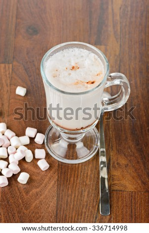 A glass of hot chocolate with marshmallows against a wooden background - stock photo