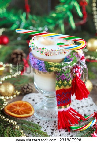 A glass of hot coffee with milk with a small knit scarf and candied orange slice on a wooden table. Christmas background with decorations. Selective Focus. - stock photo