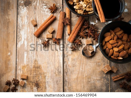 A glass of hot mulled wine, spices, cinnamon, star anise, brown sugar and nuts on a wooden board - stock photo