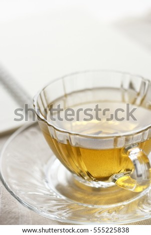 a glass of hot tea with notebook in morning light time