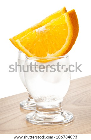 A glass of ice water or a vodka drink with a slice of orange