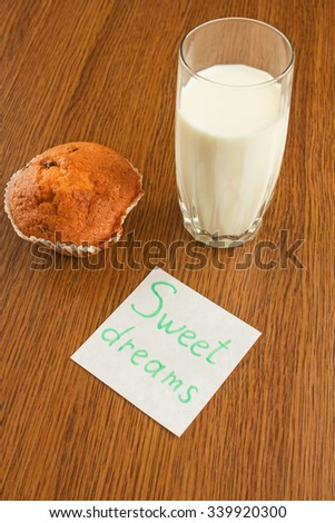 A glass of milk and  tasty muffin on wooden background. Sweet dreams. - stock photo