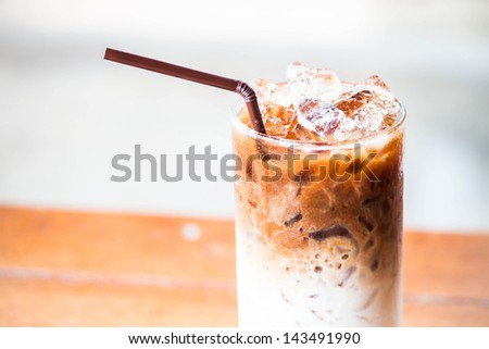 A glass of milk coffee with ice cubes - stock photo